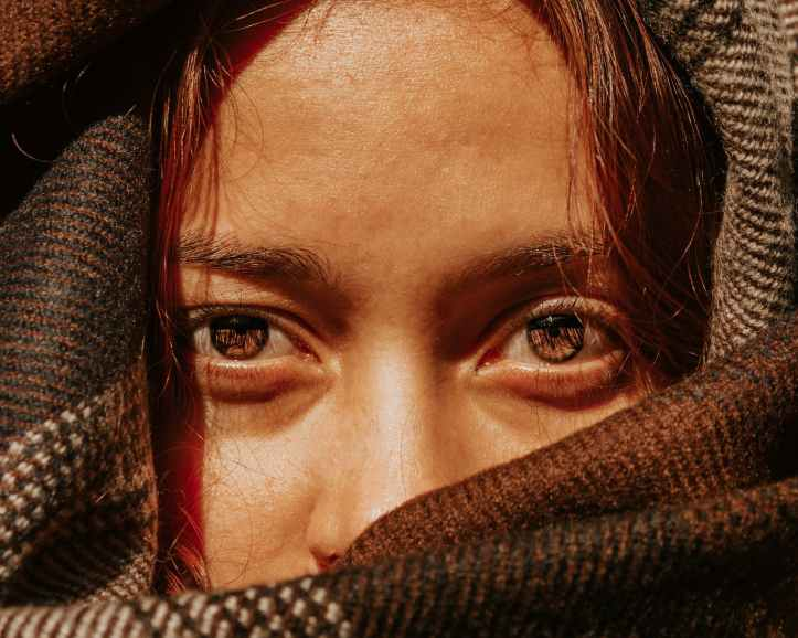 crop young woman with brown eyes in warm scarf
